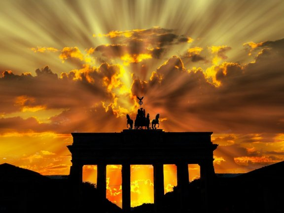 The Brandenburg Gate set against a cloudy evening sky and lights