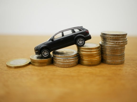 Toy car on euro coins – buying a car thanks to small VAT?